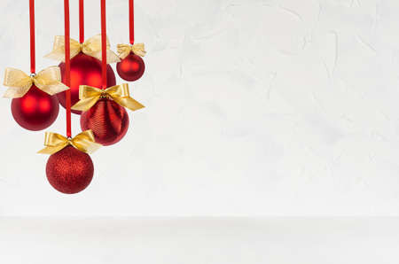 New Year background in simple style with shiny red balls with golden bows hanging on ribbon as bunch on soft light white wall and wood table, for design of poster, flyer, card, brochure, copy space. 免版税图像