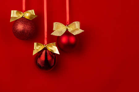 Shimmer balls with golden bows hang on ribbons in row on saturated red backdrop, copy space. Rich christmas background in modern style for design of poster, flyer, card, brochure. 免版税图像