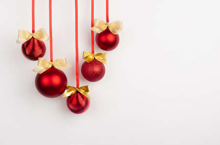 Red glossy christmas balls with gold shimmer bows hang on ribbon on white wall, copy space. Christmas background for design of poster, flyer, card, brochure.