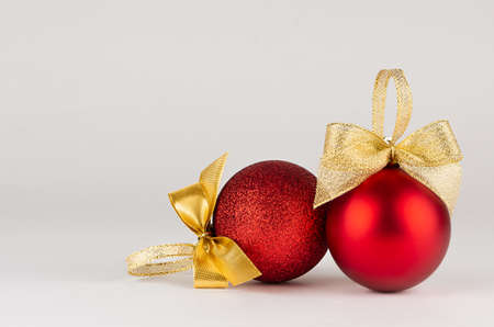 Traditional christmas background in modern simplicity style - rich shiny red balls with gold bows on white table, closeup, copy space. Backdrop for design of poster, flyer, card, brochure.