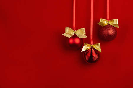 Red glossy christmas balls with gold shimmer bows hanging on ribbons in row on bright scarlet wall, copy space. Christmas background in minimal style for design of poster, flyer, card, brochure. 免版税图像