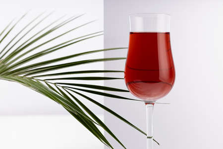 Red wine in elegant glass in sunlight with shadow in soft light white abstract minimal interior with rectangle space, closeup, crop.