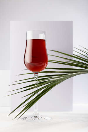 Red liquor in rich glass in sunlight with shadows, green palm leaves as decoration in soft light white abstract interior with geometric spaces, vertical.
