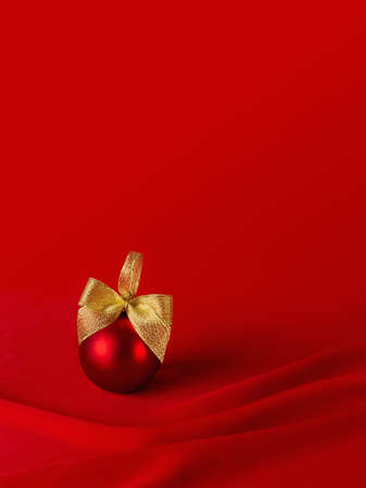 Exquisite glossy ball with golden bow on elegant dark silk backdrop with smooth waves, copy space, vertical. Rich christmas background for design of poster, flyer, card, brochure, story. 免版税图像