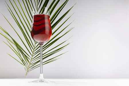 Red wine in exquisite glass in sunlight with striped curved green palm leaf with shadows in soft light white abstract interior on wood table, grey wall.