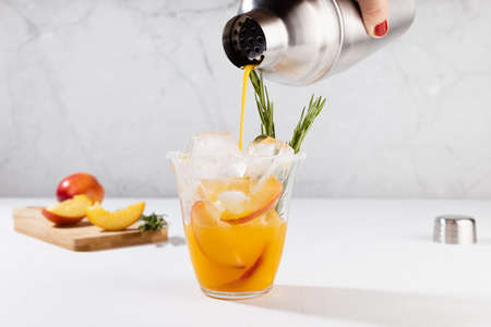 Woman's hand pour of bright refreshing summer peach alcohol cocktail of silver shaker blended with ice, green rosemary twig, sugar rim, ingredients in elegant modern white interior in sunlight. 免版税图像