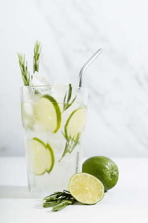 Organic mojito cocktail with citrus fruit slices, ice cubes, rosemary twig, silver straw, ingredients in transparent glass on white wood table, soft light marble wall, vertical.
