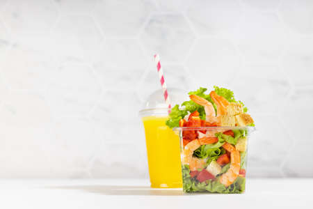 Fresh orange juice and tropical salad with shrimps, lettuce, red bell pepper, croutons in transparent plastic box on white wood table, marble tile wall. Healthy take away food set. 免版税图像