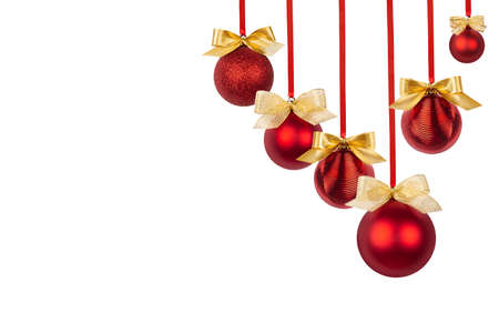 Red glossy christmas balls with gold shimmer bows hang in row on ribbons isolated on white background, copy space. Christmas background for design of poster, flyer, card, brochure. 免版税图像
