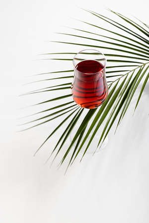 Red wine in elegant glass with green palm leaf in sunlight with striped shadows on soft light white wood table, top view, vertical. 免版税图像
