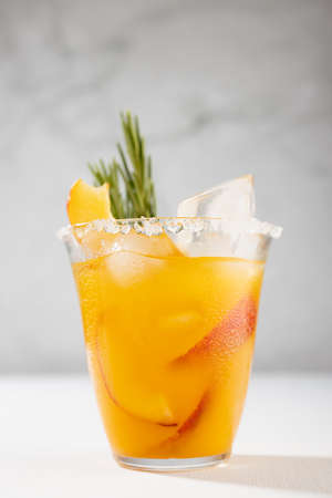 Refreshing juicy peach cocktail with ice, rosemary, sugar rim, fruit slices in misted glass on white wood table, concrete wall, vertical.