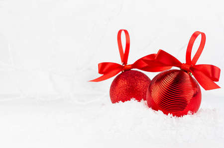 Bright christmas background - two elegant glossy glitter red balls with satin ribbon closeup in decorative fairy white winter forest, frosty branches, snow, copy space. Festive New Year background. 免版税图像