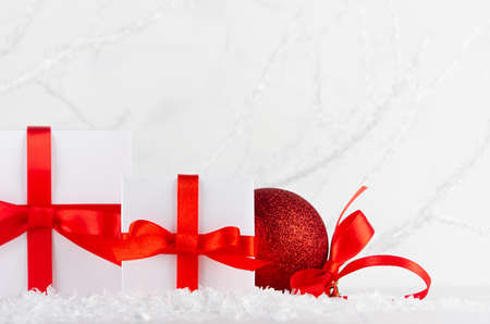 Christmas decoration - two white gift boxes and glitter red ball with satin ribbon closeup in decorative soft light winter forest with frosty branch and snow, copy space. Festive New Year background.
