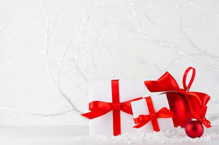 Bright christmas background - festive white gift boxes, shine red balls with red satin ribbons in decorative fairy winter forest with frosty branches, snowdrift, copy space. New Year background. 免版税图像