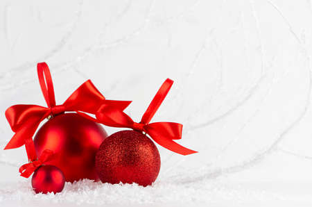 Holiday christmas background with group of sparkle red balls with ribbons, bows in decorative white winter forest in snow under frosty branches, copy space, closeup. Festive New Year background. 免版税图像