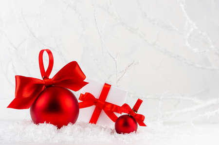 Traditional christmas decoration and present boxes with red ribbons and bows closeup in white snow in elegant soft light fairy winter forest with frosty branches, copy space. New Year background.