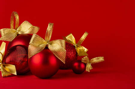 Red shiny different christmas balls with gold shimmer bow on bright deep red background, closeup, copy space. New year background in simplicity modern design for poster, flyer, card, brochure. 免版税图像