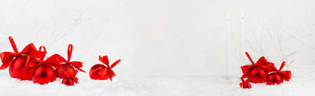 Christmas festive banner in white and red color - white burning candles, heap of rich red shimmer balls with satin ribbon, bows in snow under white frosty branches in winter forest, copy space, frame. 免版税图像