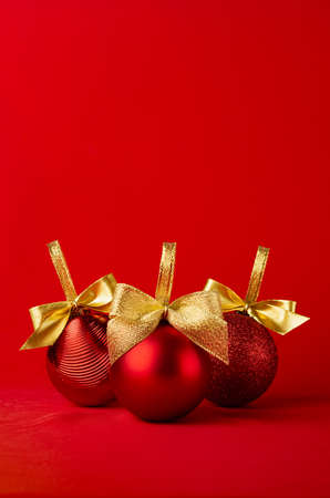 Rich christmas decoration - three balls with golden ribbon standing on saturated red background, copy space, vertical. Christmas background for design of poster, flyer, card, brochure, story.