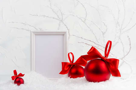 Traditional christmas background with blank photo frame mockup and rich sparkle red glossy balls with satin ribbons, bows in white snow in soft light fairy winter forest with frosty branches.