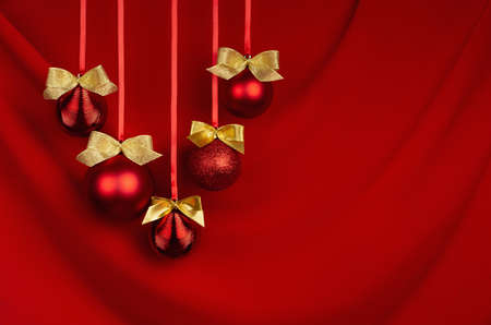 Luxury christmas decor - red balls with golden bows hanging in row on ribbons on red silk curtain with smooth waves, copy space. Christmas background for design of poster, flyer, card, brochure. 免版税图像