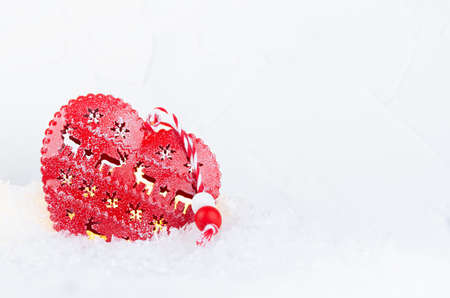Christmas background with red heart and lights glowing inside in bright shimmer snow closeup, copy space.