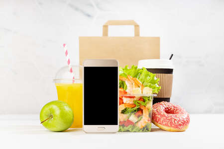 Lunch set of seafood shrimp salad in pack, orange juice, coffee cup, donut, packet, blank phone in white interior with marble tile. Mockup for advertising for delivery service, take away restaurant. 免版税图像