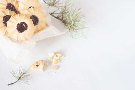 Sweet traditional christmas crumbly biscuits with jam on white wood table with green pine branches, copy space, top view. 免版税图像