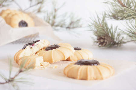 Christmas biscuits cooking with jam on white wood table with pine branches in soft light white interior, closeup.