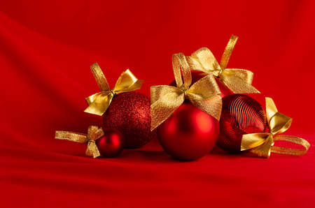 Red glossy different christmas balls with gold shimmer bows on bright silk wavy background, closeup. Christmas background for design of poster, flyer, card, brochure.