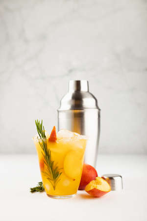 Cooking of homemade organic cold peach smoothie with ice, green rosemary twig, sugar rim, fruit slices in wet glass, ingredients, silver shaker in elegant modern white kitchen interior, vertical.