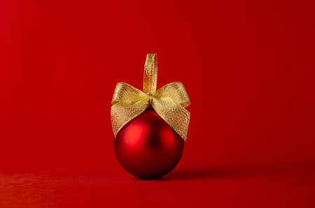 Red glossy christmas ball with gold shimmer bow on bright red background, copy space. Christmas background in modern minimal style for design of poster, flyer, card, brochure.