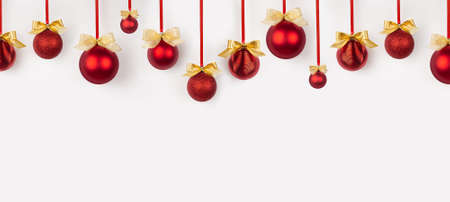 Christmas banner in simple minimal style - bright red balls with golden bows hanging on ribbon in row as pattern on soft light white wall. Background for design of website, header, card, brochure.