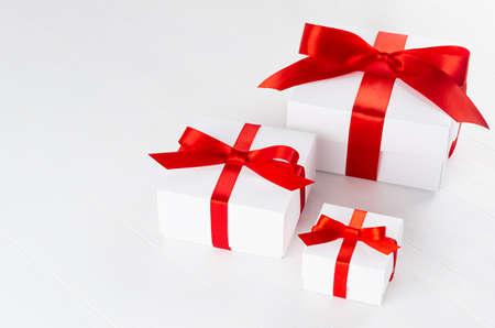 Three festive white paper boxes for gift with red silk ribbon and bow in elegant minimal style on white wood table, top view, copy space.