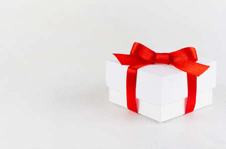 White present box with red satin ribbon and bow on white table, top view, copy space. Festive background for design of card, brochure, cover, flyer.