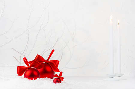 Holiday New Year background with white glowing candles, luxury rich shine red balls with bright scarlet ribbons, bows in white decorative snow and frosty branch as fairy winter forest, copy space.