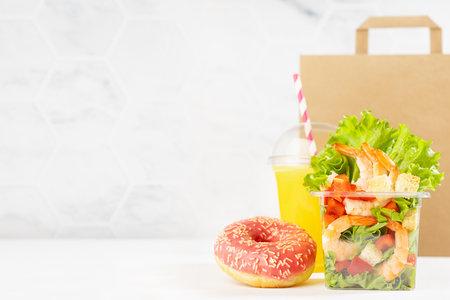 Healthy fitness food - set of orange juice, tropical shrimp salad in box, pink donut, packet in white interior. Mockup advertising for delivery service, take away restaurant, online order. 免版税图像