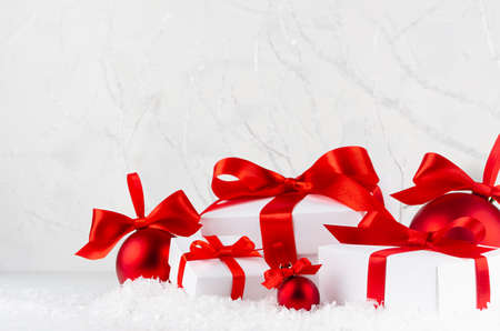 Christmas festive background in white and red color - shimmer balls and gift boxes with satin ribbon closeup in snowdrift under frosty white branches, snow in winter forest, copy space.