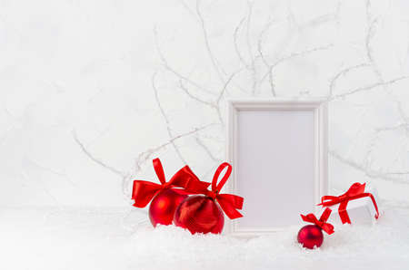 Christmas background with blank photo frame mockup for text, decorations and gift box - red glossy balls with shiny satin ribbons in decorative soft light white winter forest with frosty branch, snow.