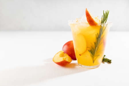 Homemade organic cold peach juice with ice, green rosemary twig, sugar rim, fruit slices in wet glass, ingredients in elegant modern white kitchen interior.