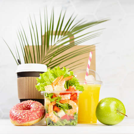 Healthy daily diet plan - set of coffee, juice, fruit, salad with shrimps in box, pink donut, packet in white interior, palm leaf, square. Advertising for restaurant take away, delivery food service.