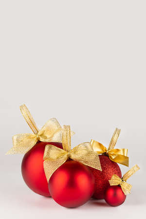 Fashion christmas background in simple minimal style - bright red balls with golden bows stand on white table with soft light wall, vertical. Backdrop for design of story, poster, flyer, card.