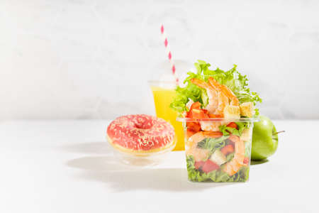 Healthy take away food set with fresh orange juice, tropical shrimp salad with lettuce, red bell pepper, croutons, green apple, pink donut in plastic pack in sunny white interior with marble wall. 免版税图像