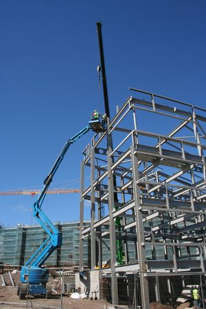 picker: Cherry picker and crane beside metal frame of new building
