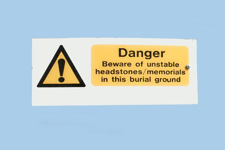 headstones: unstable headstones warning sign Stock Photo