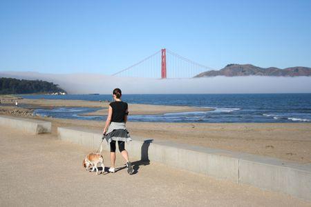 woman walking her dog in San Francisco towards Golden Gate Bridge photo
