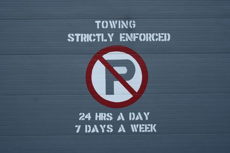 strictly: towing strictly enforced sign on garage door