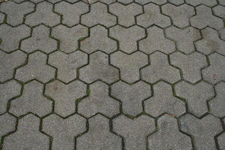 interlocking: Interlocking three pronged blocks in sidewalk background