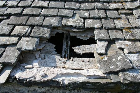 slate roof: hole in slate roof of old building Stock Photo