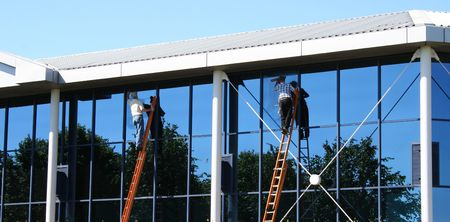 lattice window: Two window cleaners at work on office building Stock Photo